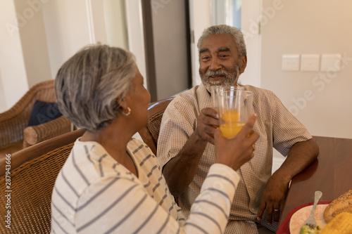 Senior couple toasting glasses of orange juice