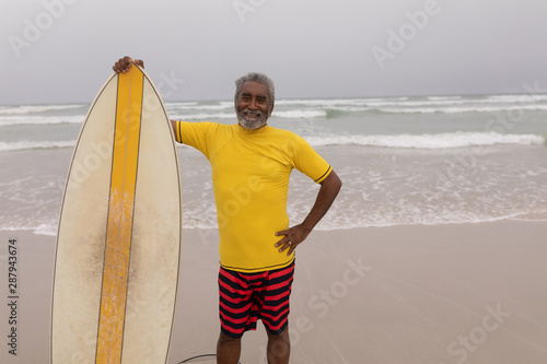 Senior male surfer standing with surfboard and looking at camera on the beach