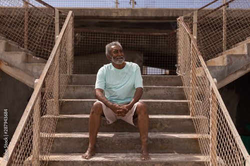 Senior man sitting on promenade stairs at beach