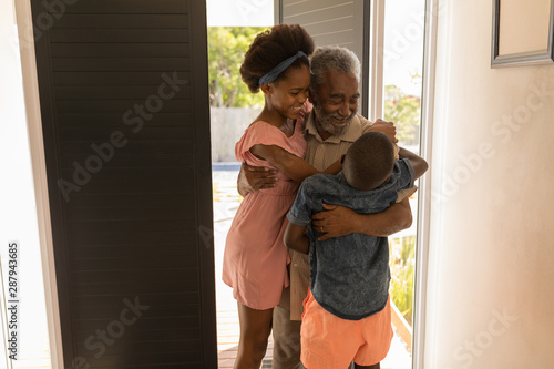 Grandfather hugging his grandchildren at home