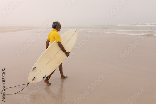 Senior male surfer walking with surfboard on the beach