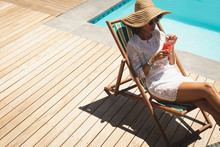 African American Woman With Cocktail Glass Relaxing On Sun Lounger In Backyard
