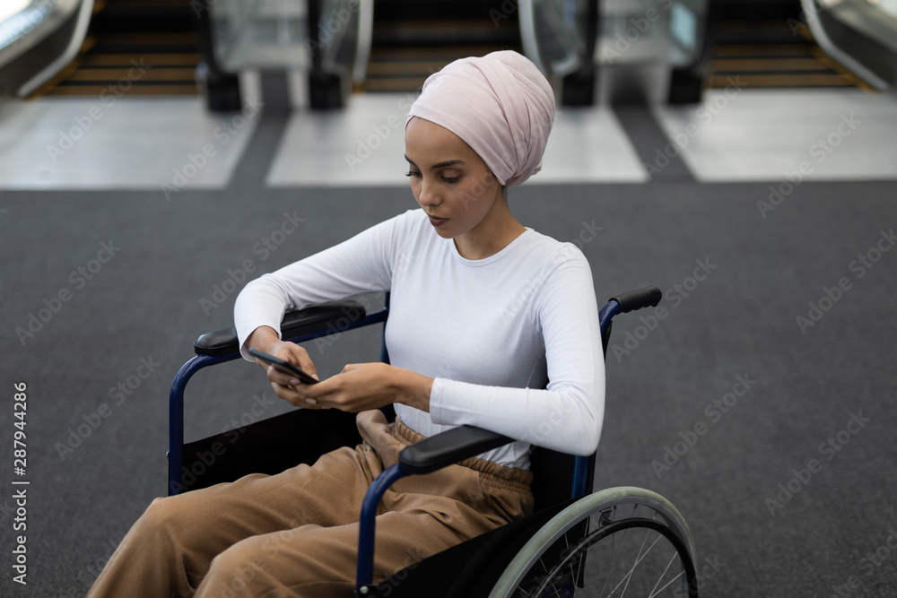 Fototapety, obrazy: Young disabled mixed-race female executive using mobile phone in the lobby