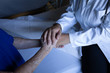 Senior female patient holding hands of doctor in hospital room