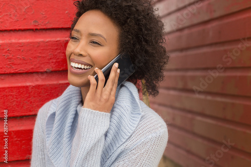 Young African American woman talking to mobile phone at beach hut