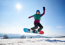 Young Female Snowboarder Jumpi...