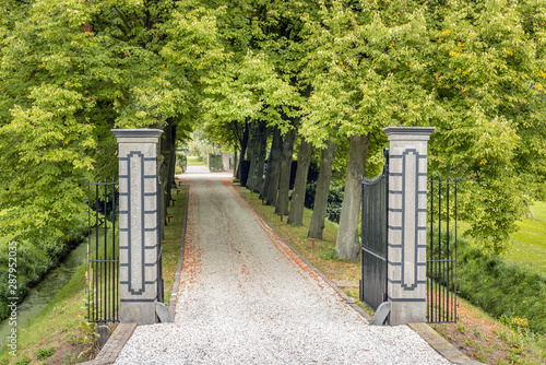 Opened black wrought iron gate to an estate