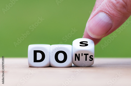 """Hand flips a dice and changes the expression """"don'ts"""" to """"does"""""""