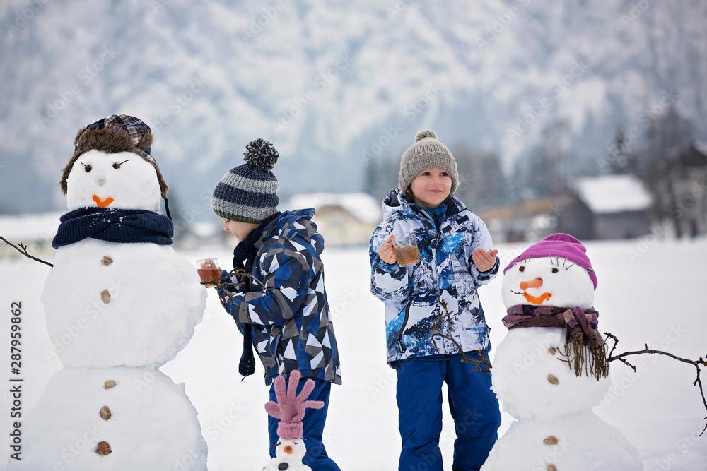 Fototapeta Family with children, building snowman in the park in little village in Austria