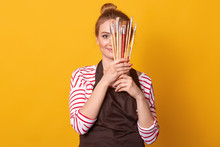 Horizontal Shot Of Girl Artist Holds Brushes In Hands And Hides Behind It, Lady Dresses Stripes Casual Shirt And Brown Apron, Blonde Woman With Bunch, Posing Isolated Over Yellow Studio Background.