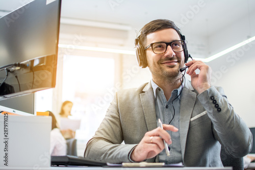 Fotomural Customer service operator man with headset listening to a client with attention