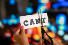Woman Hand Are Cutting Over White Paper With Scissors Over The Word Cant And Converting It To The Word Can. City Lights Bokeh As Background. Motivational And Inspiraton Concept.