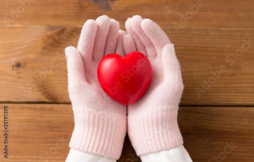 La pose en embrasure Fleur winter, valentine's day and christmas concept - hands in pale pink woollen gloves holding red heart over wooden boards background