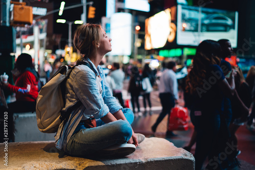 Εκτύπωση καμβά Hipster girl sitting on Times square with smartphone sending photos from landmar