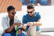 canvas print picture - leisure, technology and people concept - happy male friends with smartphones drinking beer and talking on street in summer