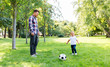 Leinwanddruck Bild - family, fatherhood and people concept - happy father and little son with ball playing soccer at summer park