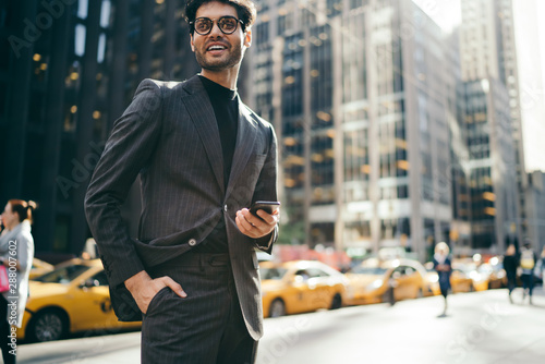 Fototapeta Cropped portrait of successful young entrepreneur dressed in fashionable formal wear smiling at camera while strolling on New York street near office building with modern smartphone in hands obraz