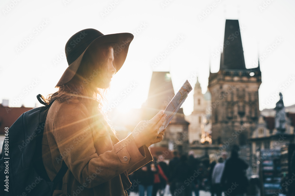 Fototapety, obrazy: Girl with backpack looking at map. Girl visiting the sights Praha in holiday.