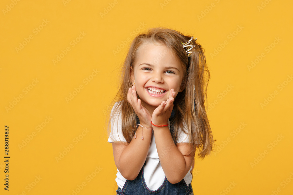 Fototapeta Little cute child kid baby girl 4-5 years old wearing light denim clothes isolated on pastel yellow wall background, children studio portrait. Mother's Day, love family, parenthood childhood concept.
