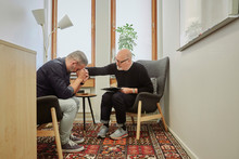 Therapist Consoling Mature Patient During Therapy Session