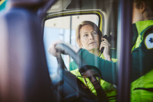 Paramedic Talking On Phone While Looking At Coworker In Ambulance