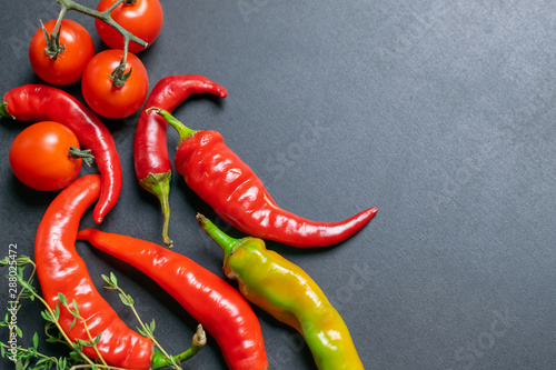 La pose en embrasure Hot chili Peppers Fresh hot red chili peppers and tomatoes on a slate board, cooking ingrediens on a slate board