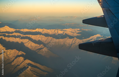 Mountain range seen from Airplane, with plane wing seen on the right side Canvas Print