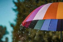 Bright Colored Rainbow Umbrella In The Rain Weather