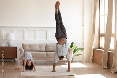 Stampa su Tela  Smiling black family doing morning exercises together at home.