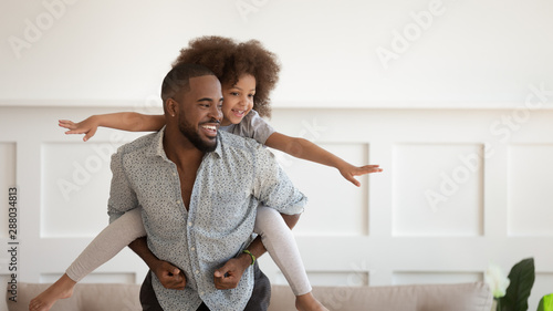 Photo Excited black man giving piggyback ride to happy cute daughter.