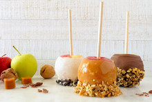 Three Types Of Autumn Candy Apples With Caramel And Chocolate Against A Bright Wood Background