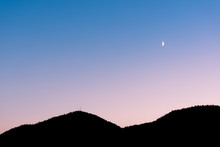 Crescent Moon In Sunset Sky Above Sillhouette Of Mountains