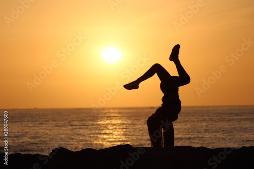 Photo  Silhouette of a female holding a yoda pose with a blurred sea and clear sky in t