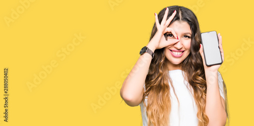 Obraz Young adult woman showing smartphone screen with happy face smiling doing ok sign with hand on eye looking through fingers - fototapety do salonu