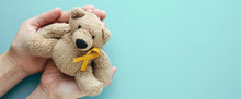 Hands Holding Children Soft Toy Brown Bear With Yellow Gold Ribbon, Childhood Cancer Awareness