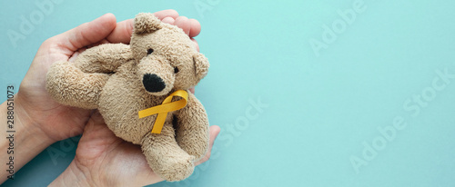 Hands holding children soft toy brown bear with yellow gold ribbon, Childhood ca Canvas Print