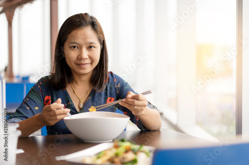 Cuadros en Lienzo Asian woman sit near the window and happy enjoy with chineses noodle food
