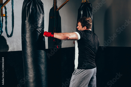 Muscular kickbox fighter exercising with punch bag at the gym Wallpaper Mural
