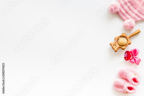 Obraz Booties and hat for newborn girl with rattle and dummy on white background top view mock up - fototapety do salonu