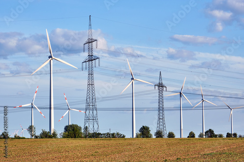 Wind turbines and power lines behind an acre seen in Germany Canvas Print