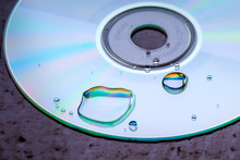 Closeup Of Water Drops Refracting Light On CD.