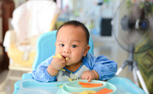 Asian Baby Boy 6 Months Old Eating With Baby Led Weaning (BLW) Method, Self-Feeding