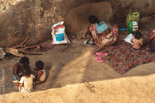 Photo A poor family of six people living on the floor at the roadside with bare essentials