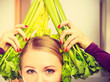 Leinwanddruck Bild - Woman in kitchen holds green celery
