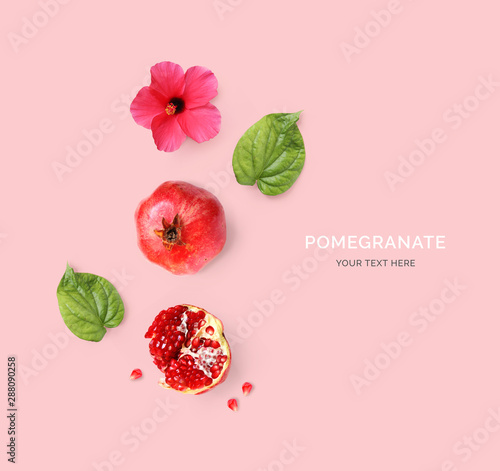Creative layout made of pomegranate, pink flower and green leaves on pink background. Flat lay. Food concept. Macro  concept. - 288090258