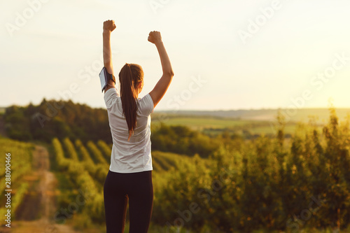 Obraz Girl raised her hands up at a training on the nature on the morning. - fototapety do salonu