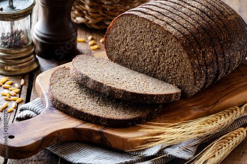 Photo Stands Bread Sliced rye bread on a rustic cutting board with grain and rye ears at the background