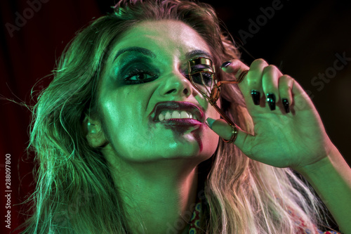 Fototapety, obrazy: Woman dressed as joker using a eyelash curler