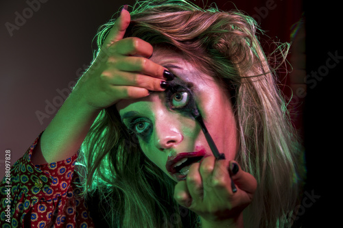 Fototapety, obrazy: Woman dressed as clown using make-up