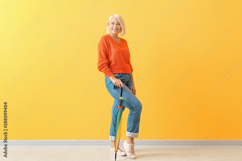 Fototapety, obrazy: Stylish mature woman with umbrella against color wall